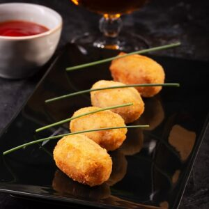 Tapas croquettes, traditional Spanish or French snack on a dark background
